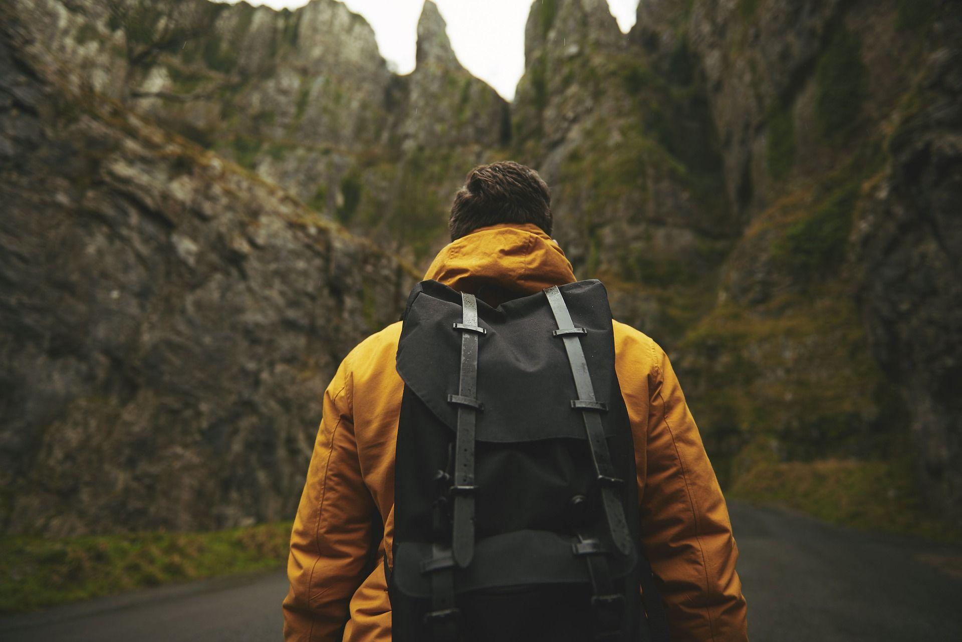 אדם במעיל צהוב נושא תרמיל מול ההרים, צילום: Pixabay