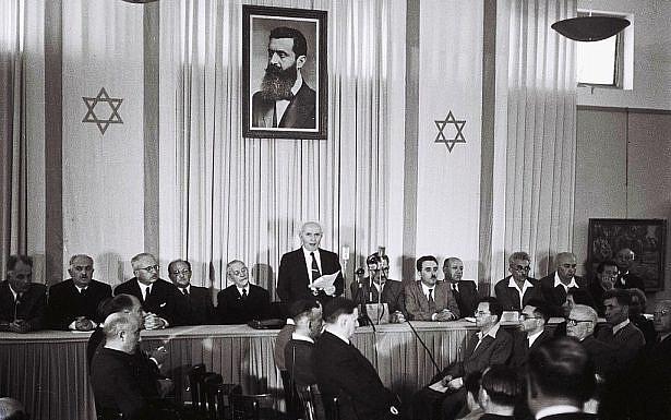 בן גוריון מכריז על הקמת מדינ תנת ישראל כשברקע תמונת הרצת ושני דגלי המדינה בצדדים. צילום: ויקיפדיה