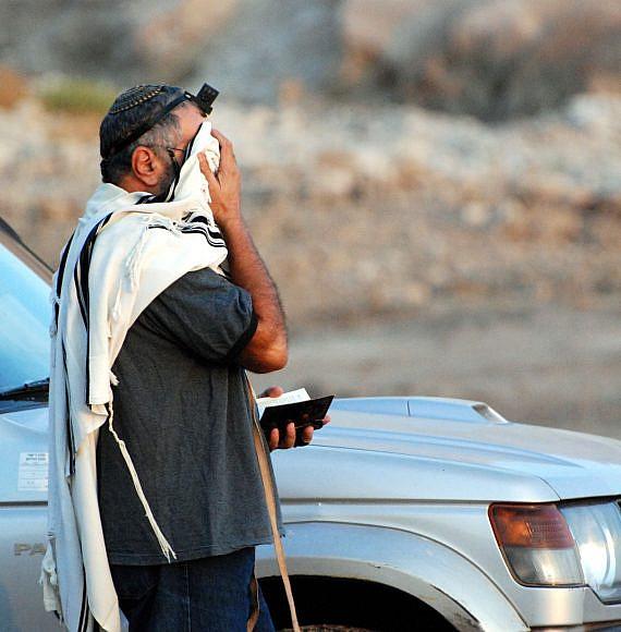 גבר עם טלית ותפילין מתפלל לצד רכב, צילום: Pixabay