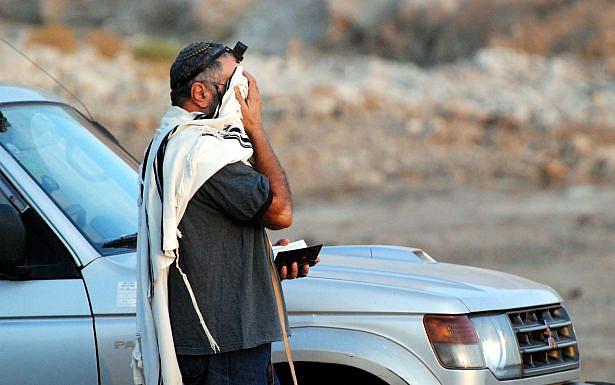 גבר עם טלית ותפילין מתפלל לצד רכב