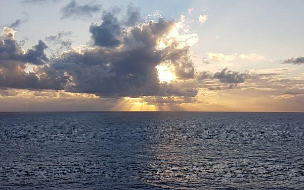 שמש מציצה מבעד לעננים מעל הים, צילום: Pixabay
